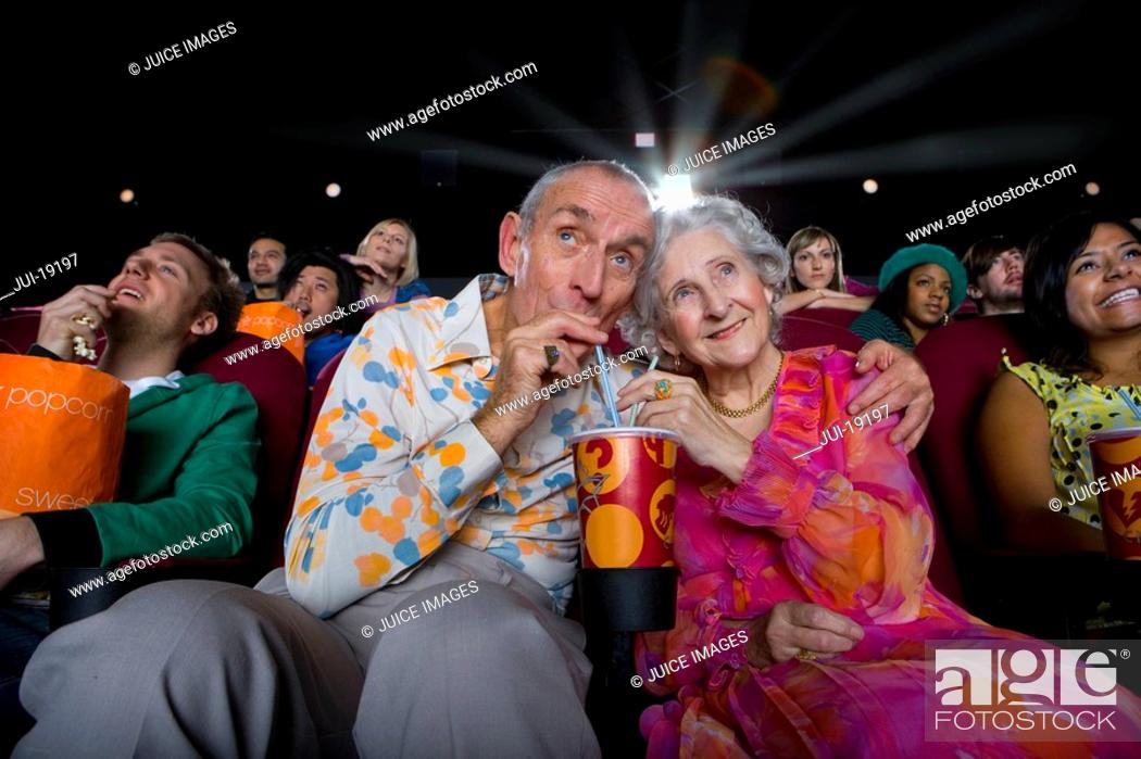 Stock Photo: Senior couple sharing drink in cinema, low angle view.