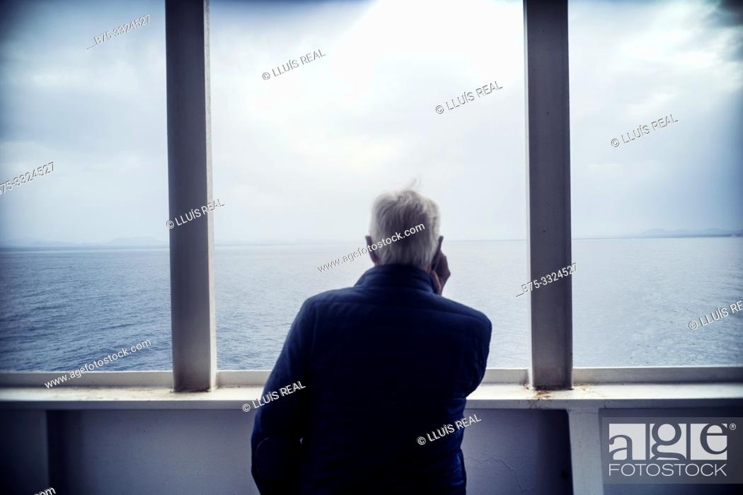 Stock Photo: A man from behind on the deck of a boat looking at the sea. Mediterranean Sea,.