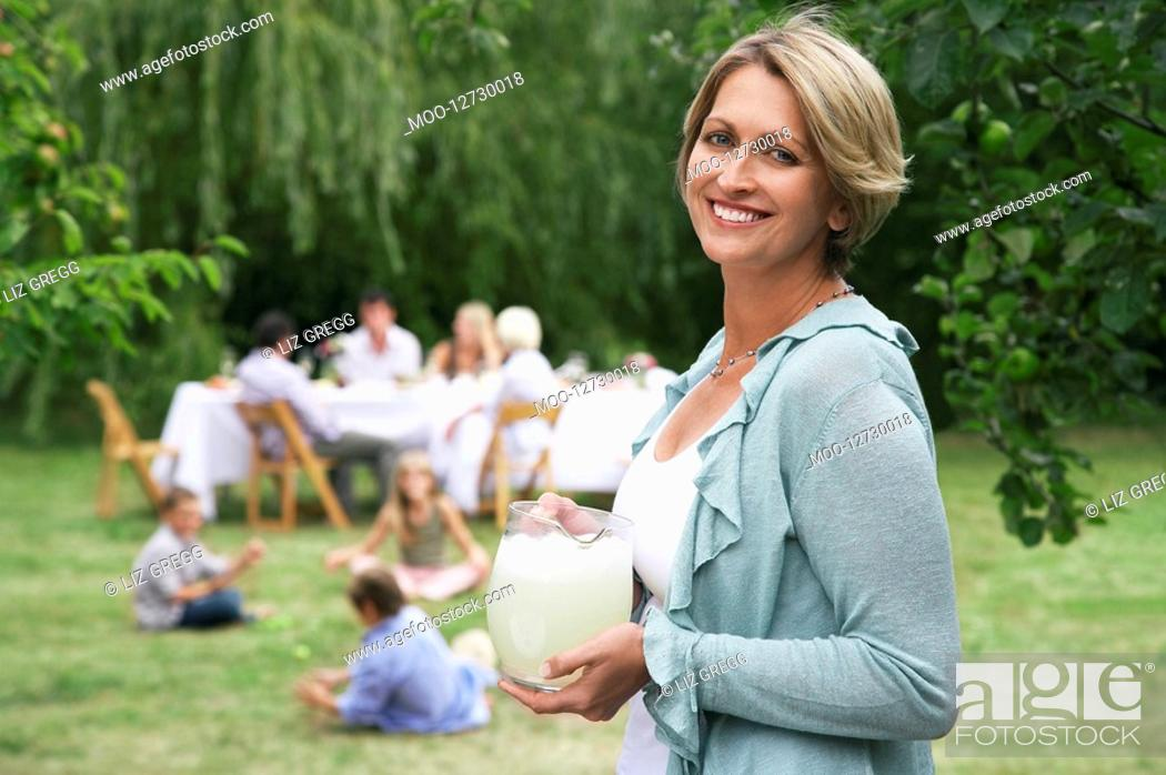 Stock Photo: Woman with pitcher of lemonade in garden family members in background.
