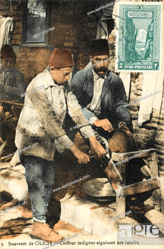 Stock Photo: A barber sharpens his razors on a grindstone turned by his young assistant - Adana, Turkey.