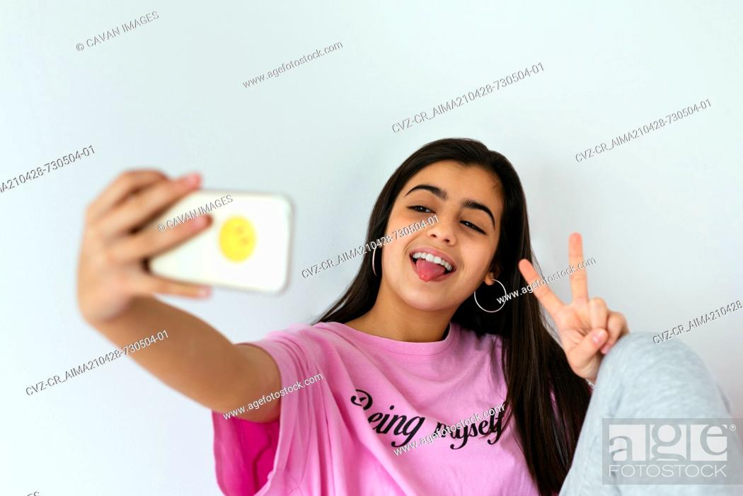 Stock Photo: Teenage girl using smartphone on bed and taking photos.