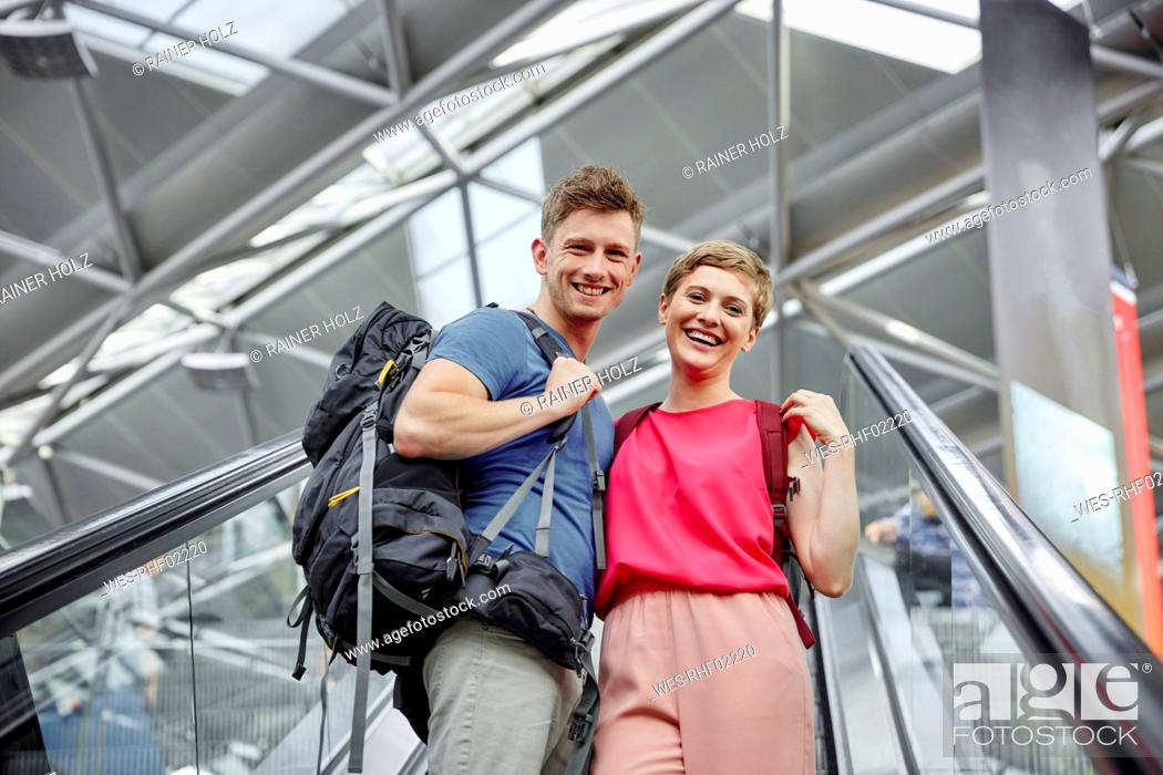 Stock Photo: Happy couple on escalator at the airport.