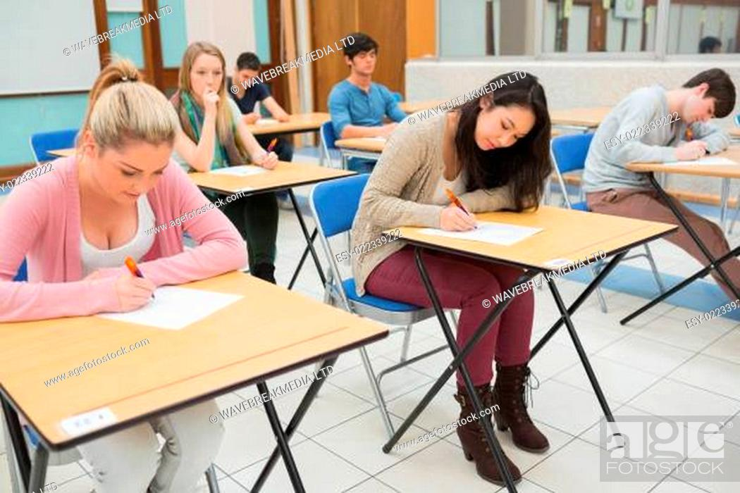 Stock Photo: People sitting at the classroom while writing.