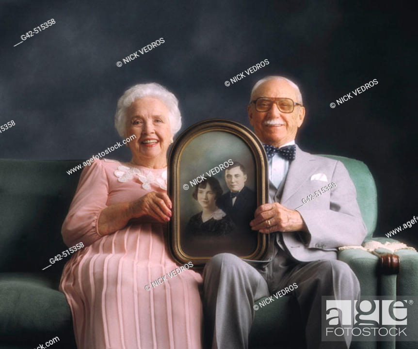 Stock Photo: Elderly couple holding photo from when they were just married.