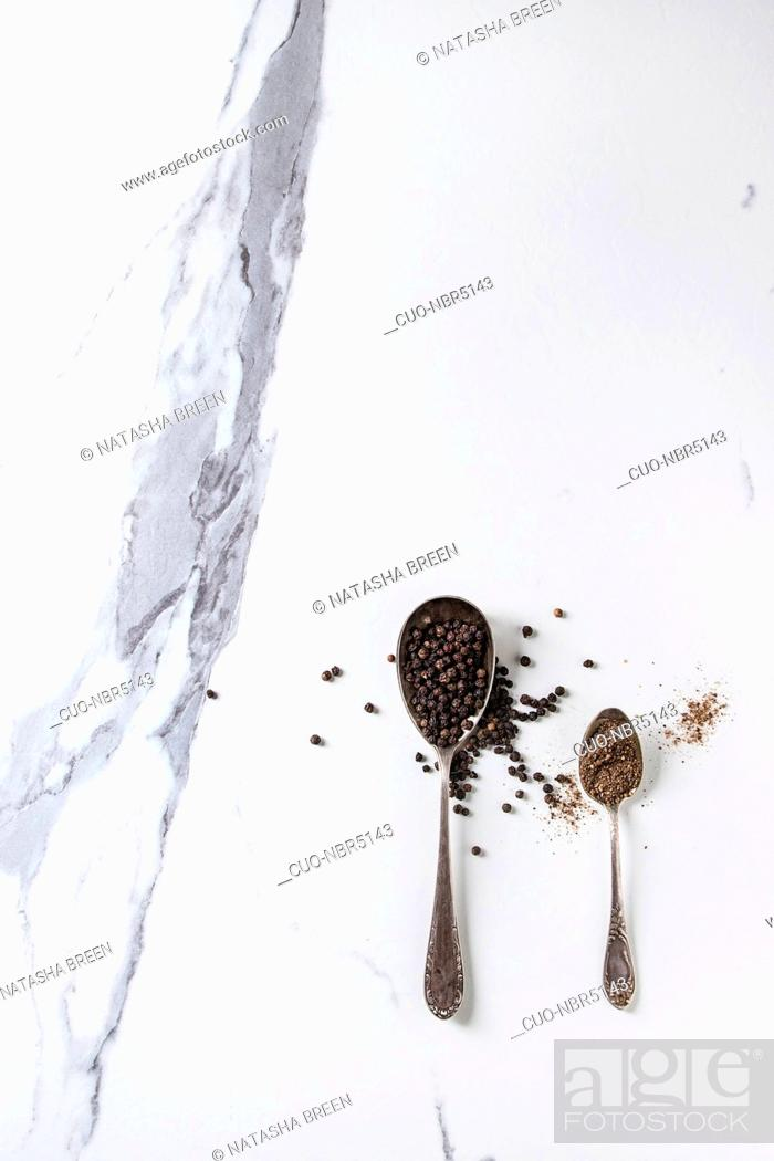 Stock Photo: Black pepper peppercorns and ground powder in vintage spoons over white marble texture background. Top view, space.