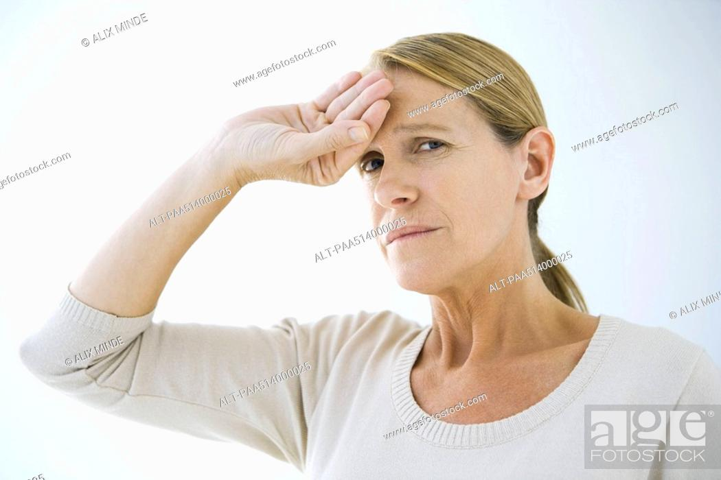 Stock Photo: Woman holding hand on her forehead, frowning at camera.