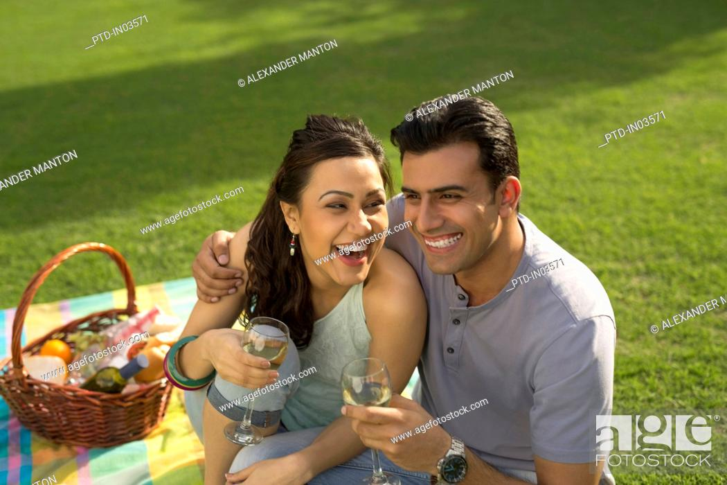 Stock Photo: Man and woman sitting on picnic blanket laughing.