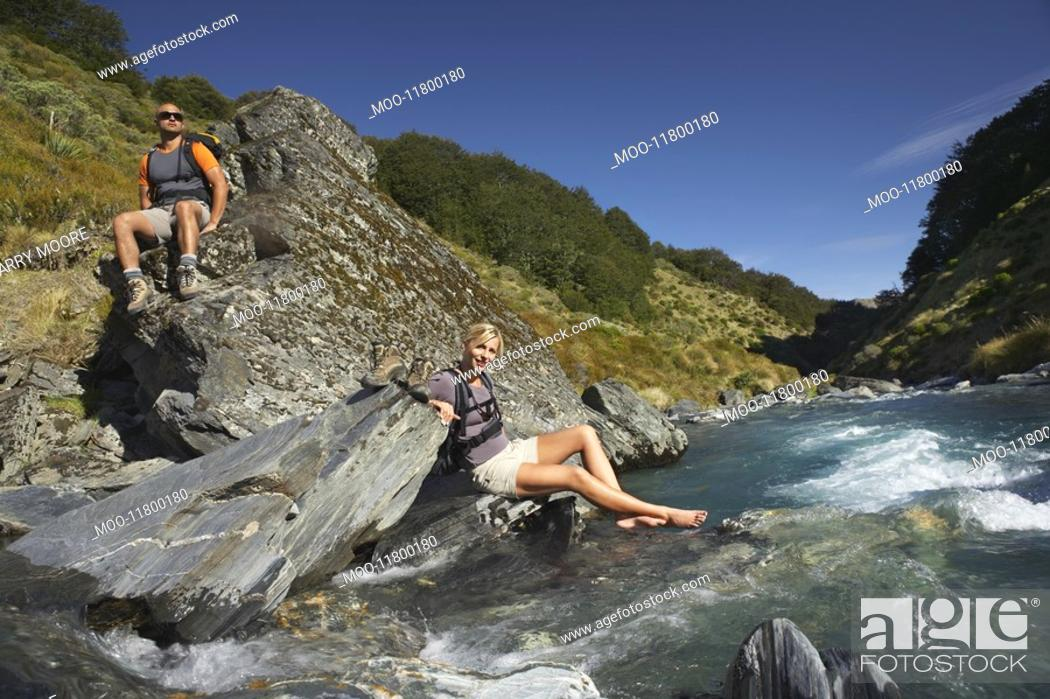 Stock Photo: Hikers relaxing by river.