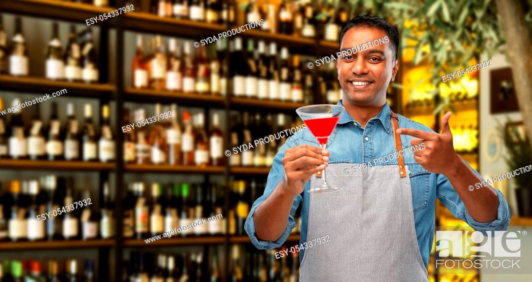 Stock Photo: indian barman with glass of cocktail at bar.