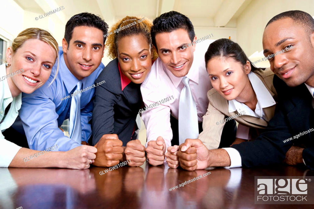 Stock Photo: Portrait of a group of business executives with their fists on a table.