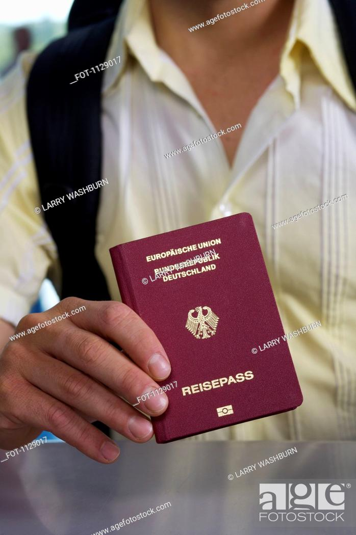 Stock Photo: Detail of a man holding a German passport.
