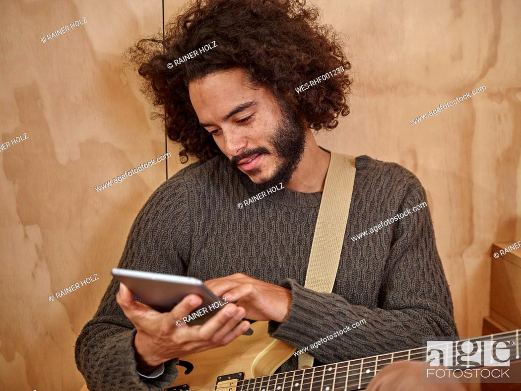Imagen: Young man with electric guitar looking at digital tablet.