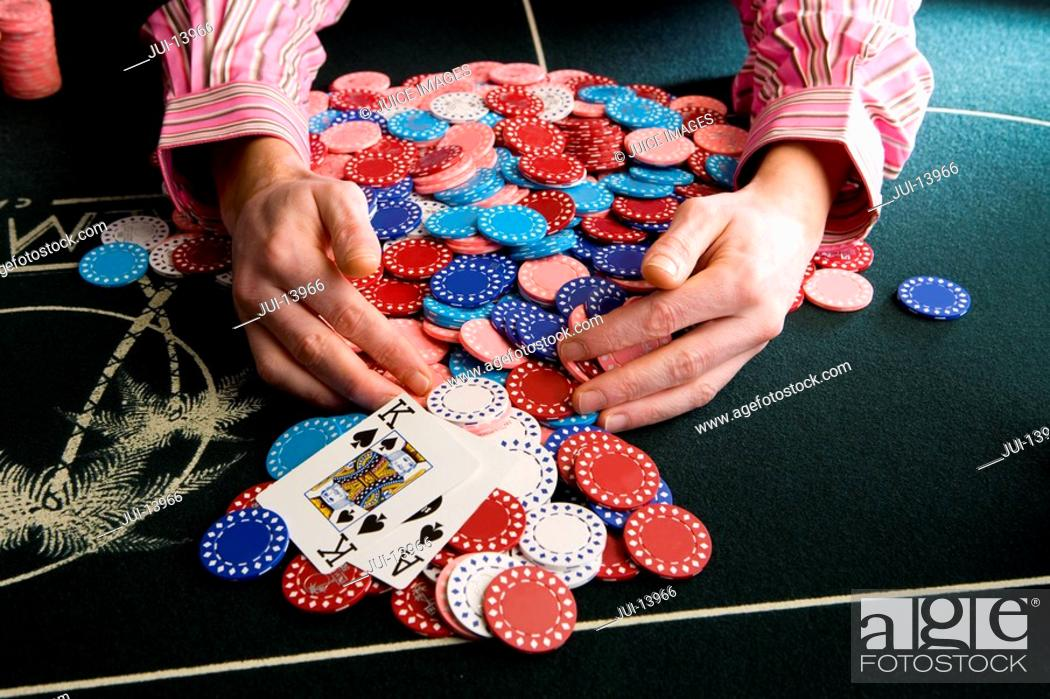 Stock Photo: Man collecting pile of gambling chips on table, close-up.