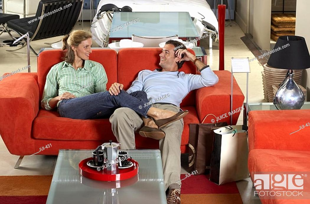 Stock Photo: Couple testing new red sofa in furniture store, woman sitting with feet up on man's lap, smiling.