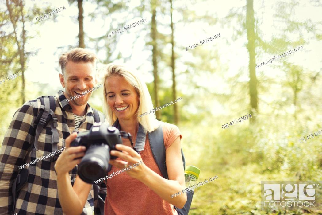 Stock Photo: Smiling couple hiking, viewing digital SLR camera in woods.