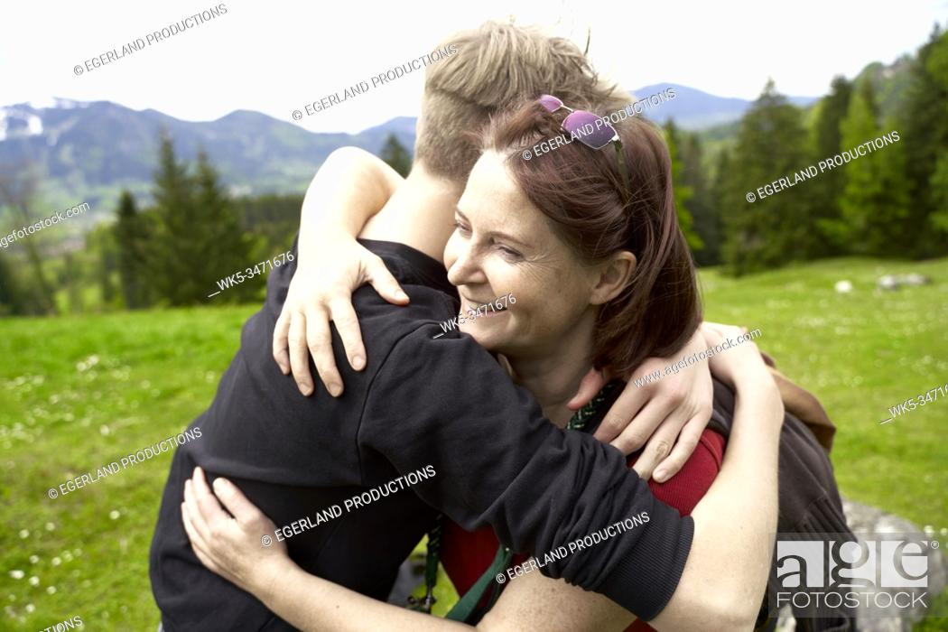 Imagen: Mature woman and teenager son in the countryside, embracing. Bad Tölz, Upper bavaria, Germany.