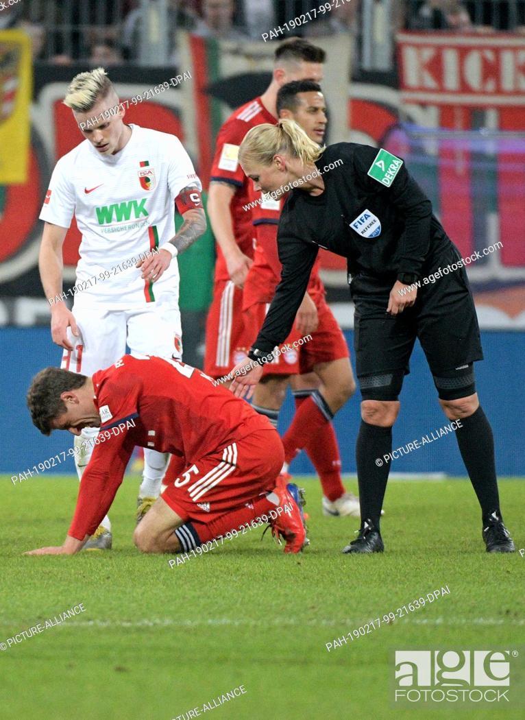 Stock Photo: 15 February 2019, Bavaria, Augsburg: Soccer: Bundesliga, FC Augsburg - FC Bayern Munich, 22nd matchday in the WWK-Arena. Referee Bibiana Steinhaus bends over to.
