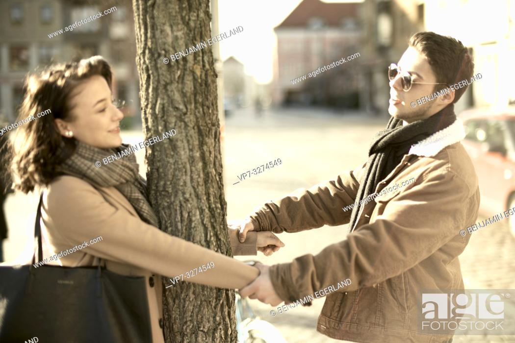 Stock Photo: young teenage couple holding hands around tree, in city Cottbus, Brandenburg, Germany.