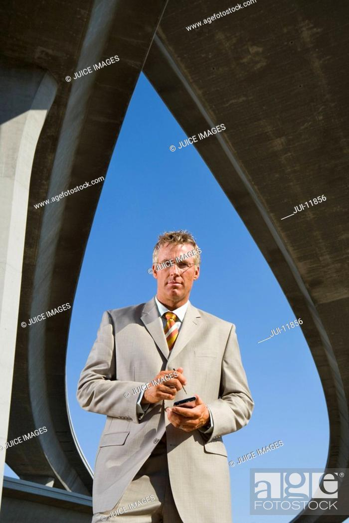 Stock Photo: Businessman with electronic organiser beneath overpasses, portrait, low angle view.