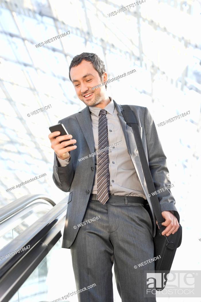 Stock Photo: Germany, Leipzig, Businessman using cell phone on escalator, smiling.