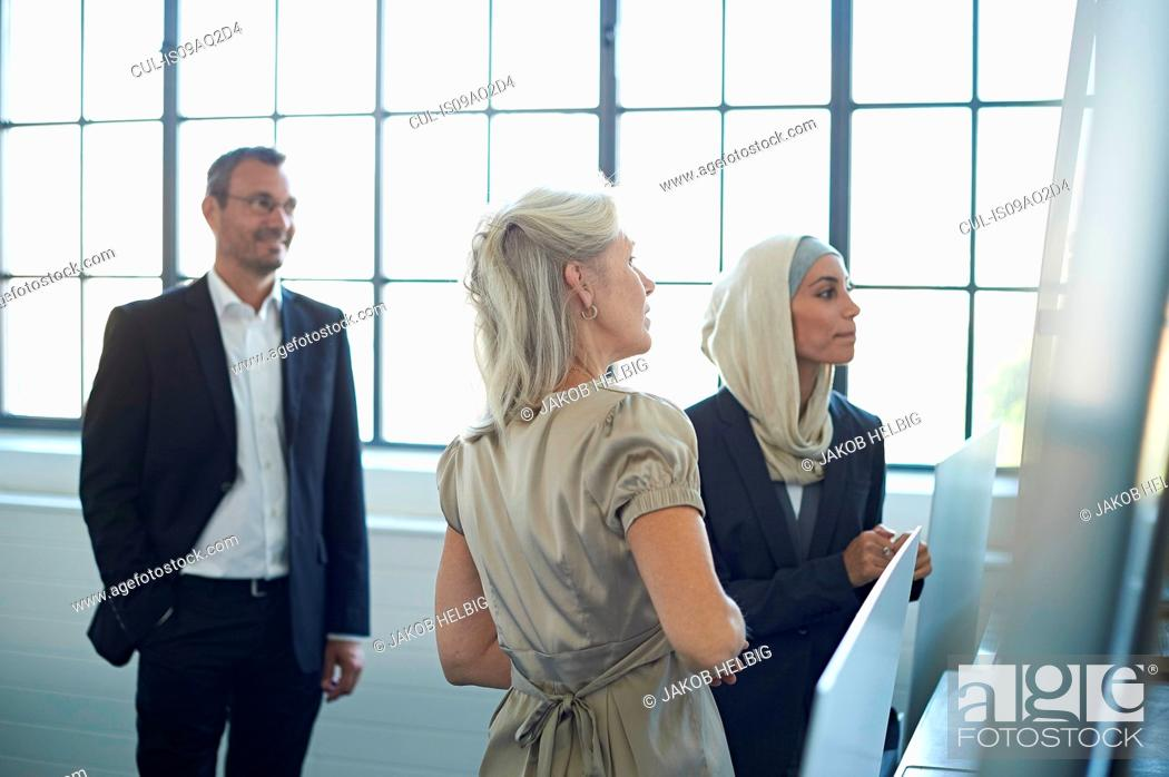 Stock Photo: Business team presenting ideas in office.