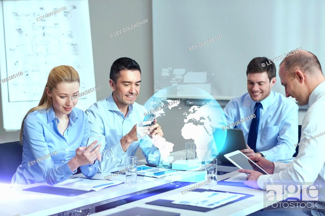 Stock Photo: business, people, cooperation and technology concept - smiling business team with gadgets and globe hologram meeting in office.