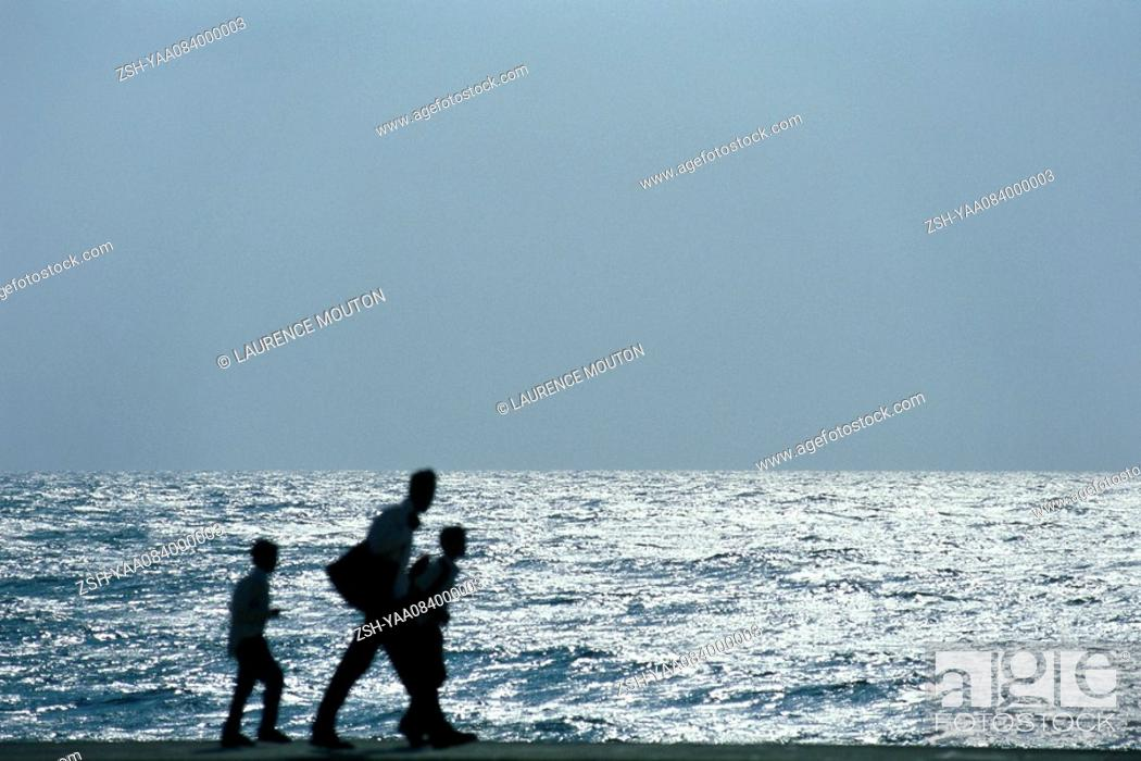 Stock Photo: Man walking with two sons, silhouetted against ocean.
