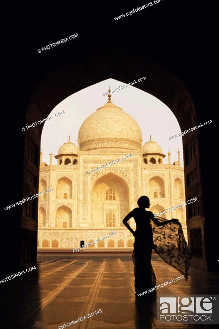 Stock Photo: Silhouette of a woman standing in front of a mausoleum, Taj Mahal, Agra, Uttar Pradesh, India.