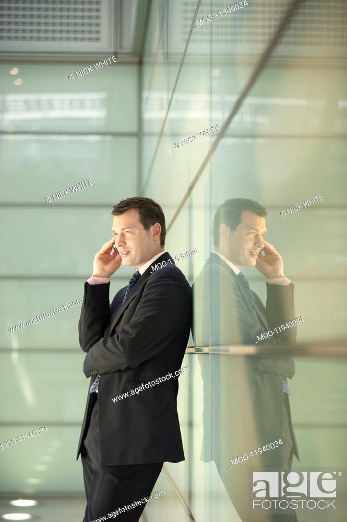 Stock Photo: Businessman Using Cell Phone in Office Corridor.