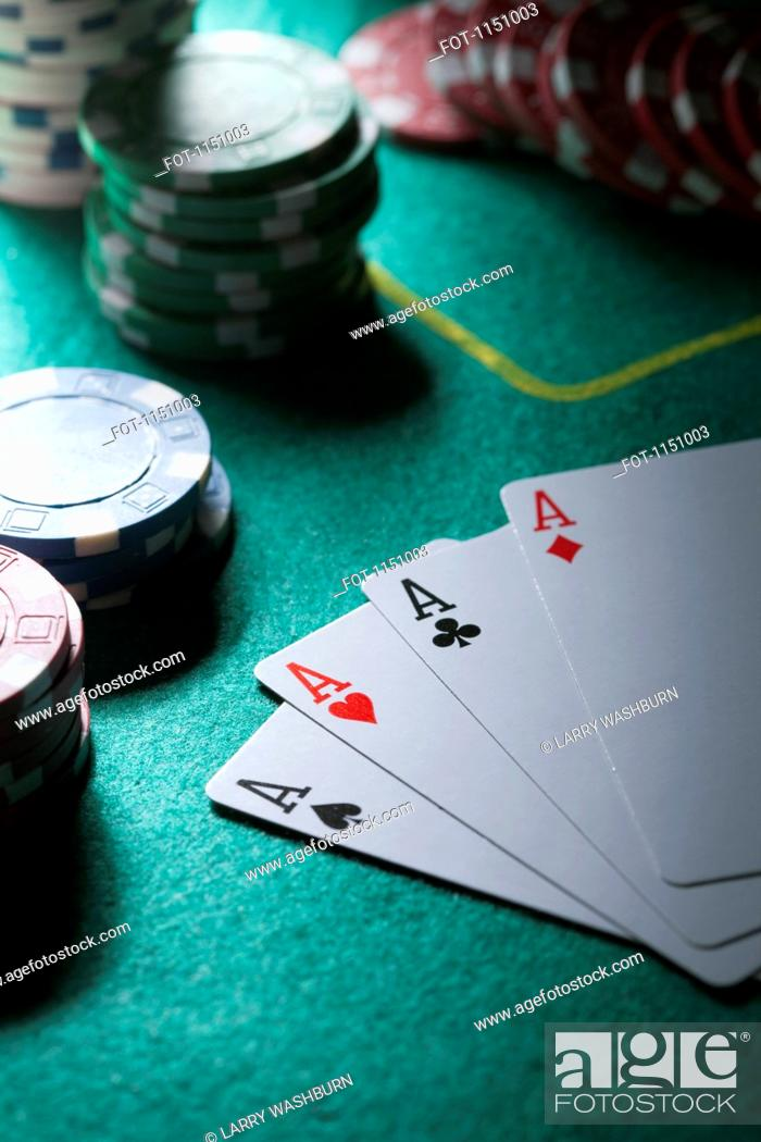 Stock Photo: A hand of cards displaying four aces, gambling chips in background.