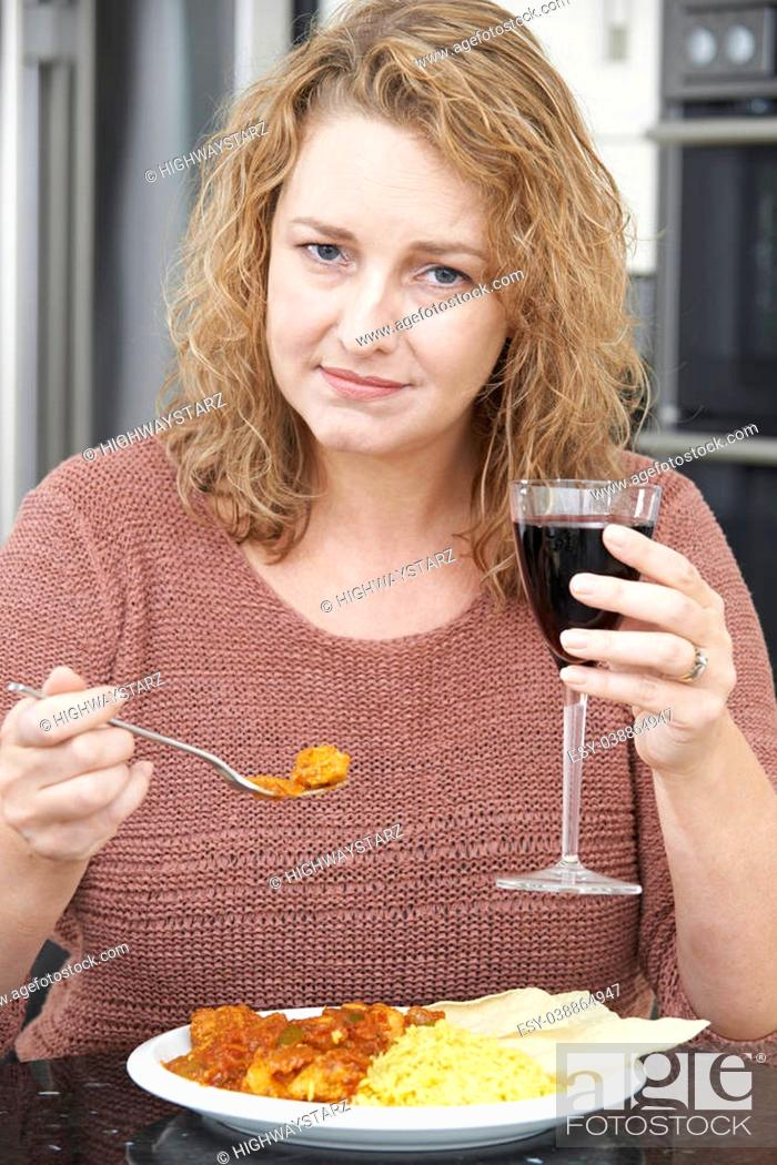 Stock Photo: Guilty Woman Eating Takeaway Curry And Drinking Wine.
