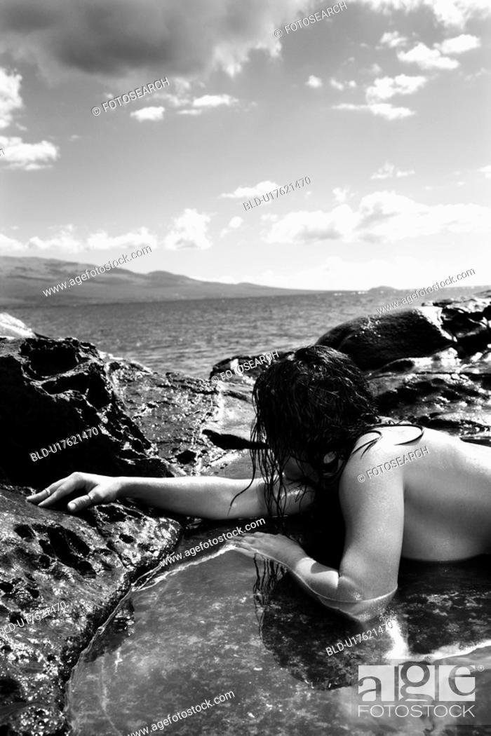 Stock Photo: Close up of nude Caucasian mid adult woman lying in tidal pool at coast looking toward ocean.