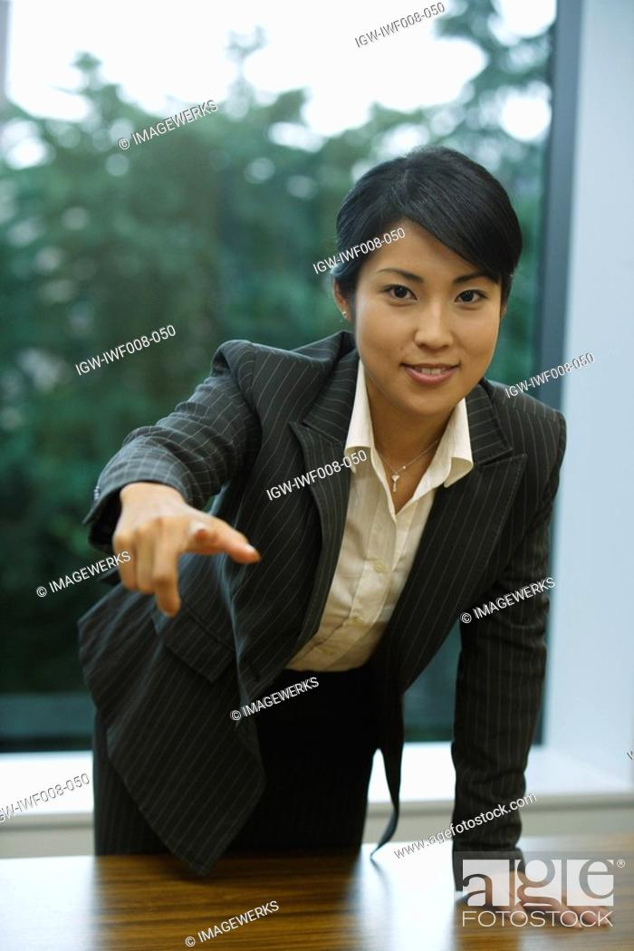 Stock Photo: A professional woman pointing towards something as she smiles at the camera.