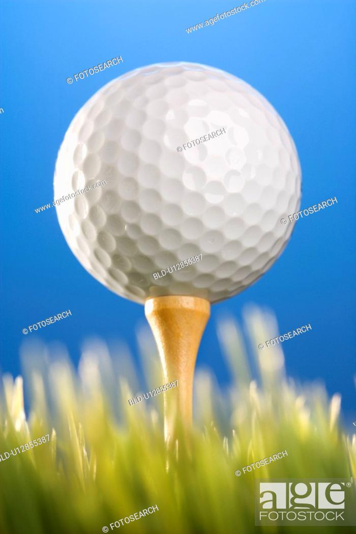 Stock Photo: Studio shot of a golf ball on a tee in grass.