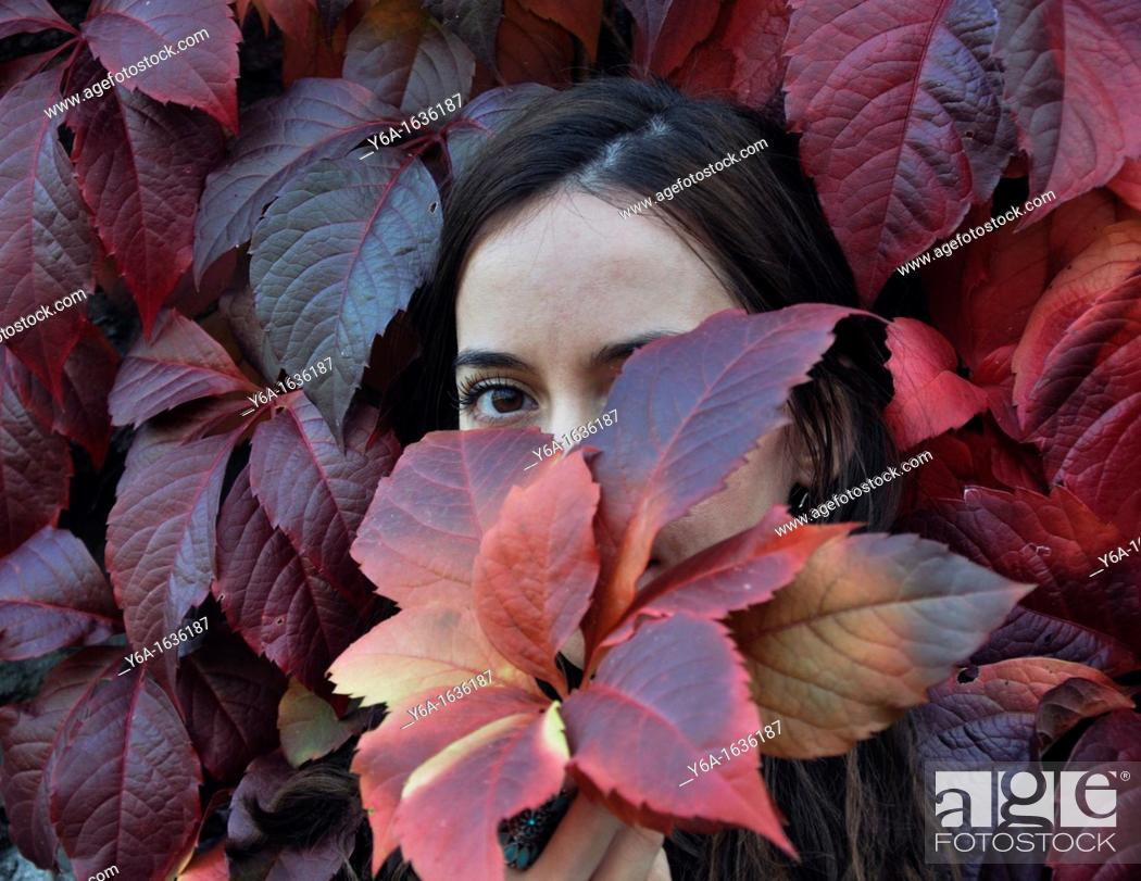 Stock Photo: Portrait of a young woman outdoors holding ivy leaf in front of face.