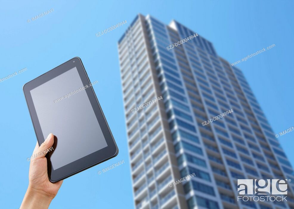 Stock Photo: High-rise condominium and a tablet PC.