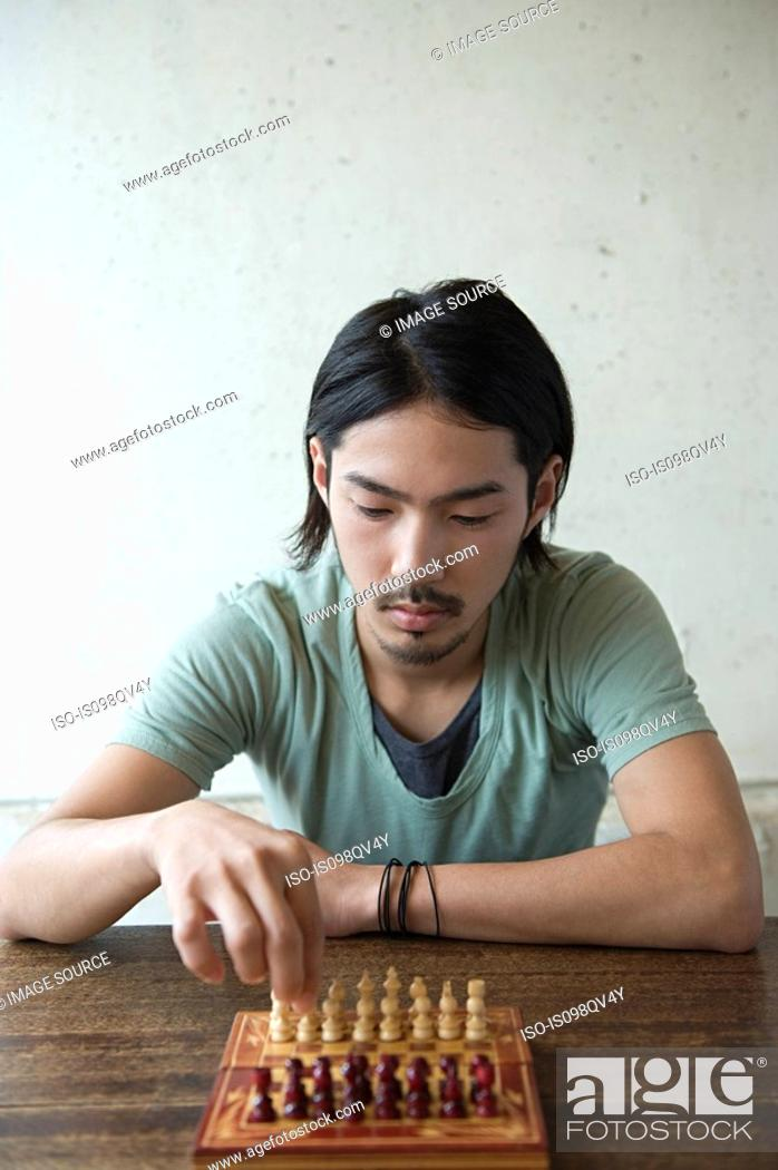 Stock Photo: Young man playing chess.