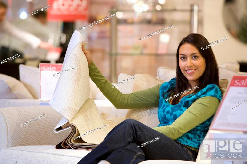 Stock Photo: Young woman looking at fabic samples in shop, smiling, portrait.