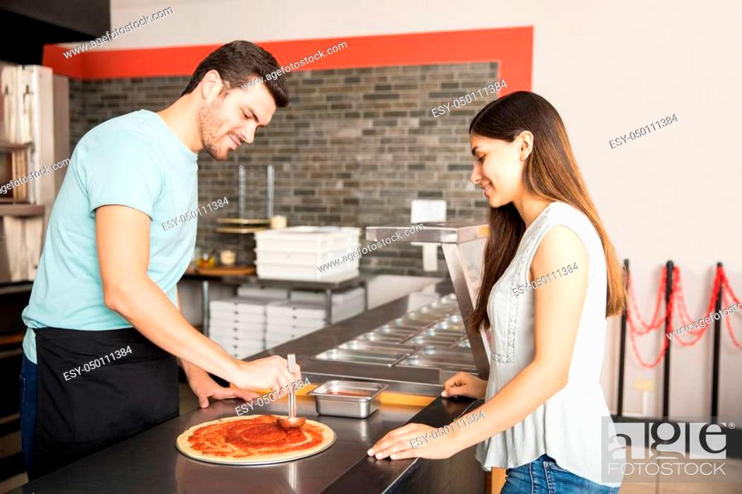 Stock Photo: Professional chef preparing italian pizza while customer standing at counter.