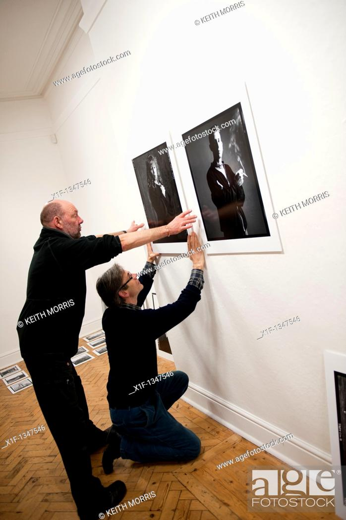 Stock Photo: Setting up an exhibition of portrait photographs in an Art gallery, UK.