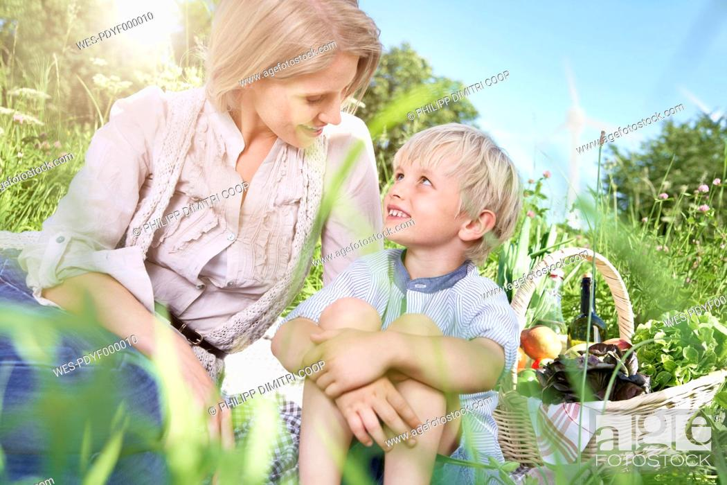 Stock Photo: Germany, Cologne, Mother and son sitting on blanket at picnic, smiling.
