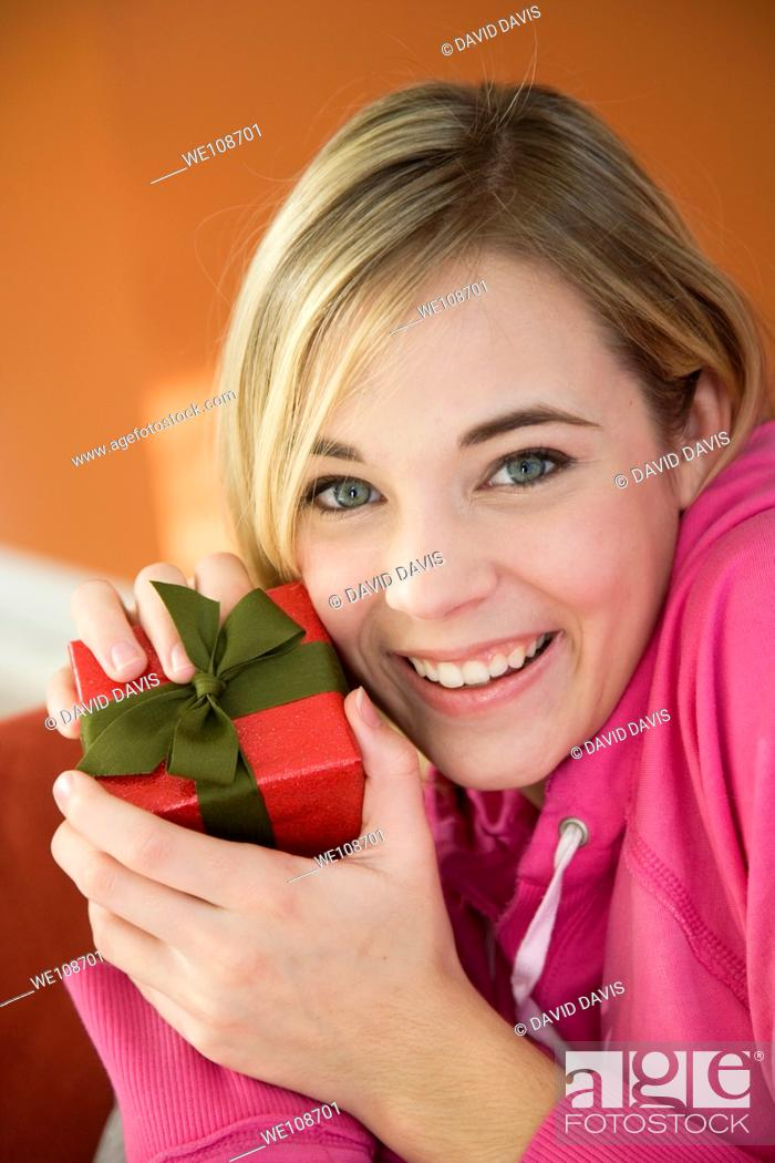 Stock Photo: Young woman excited after recieving a special gift.
