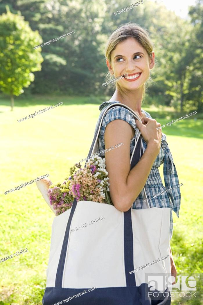 Stock Photo: Woman in park with bag.