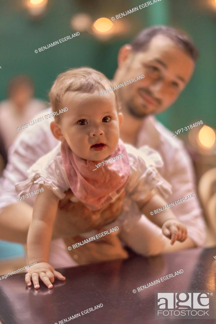 Stock Photo: father with baby at table in restaurant, Vegan Oriental, Kismet, in Munich, Germany.