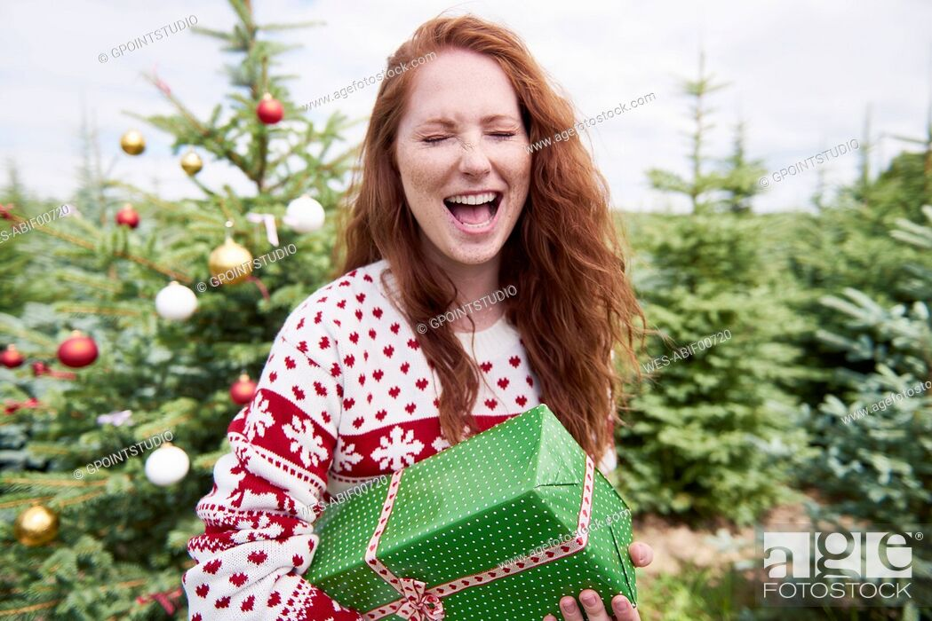 Photo de stock: Portrait of redheaded woman with Christmas present crying of joy.