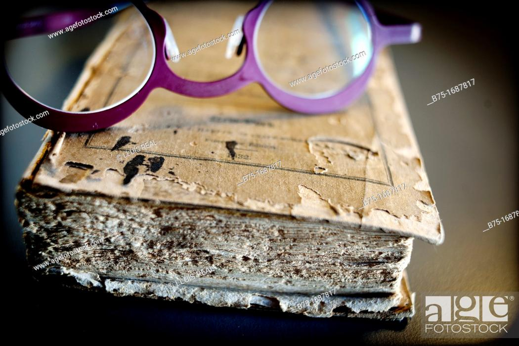Stock Photo: Old book with glasses for reading.
