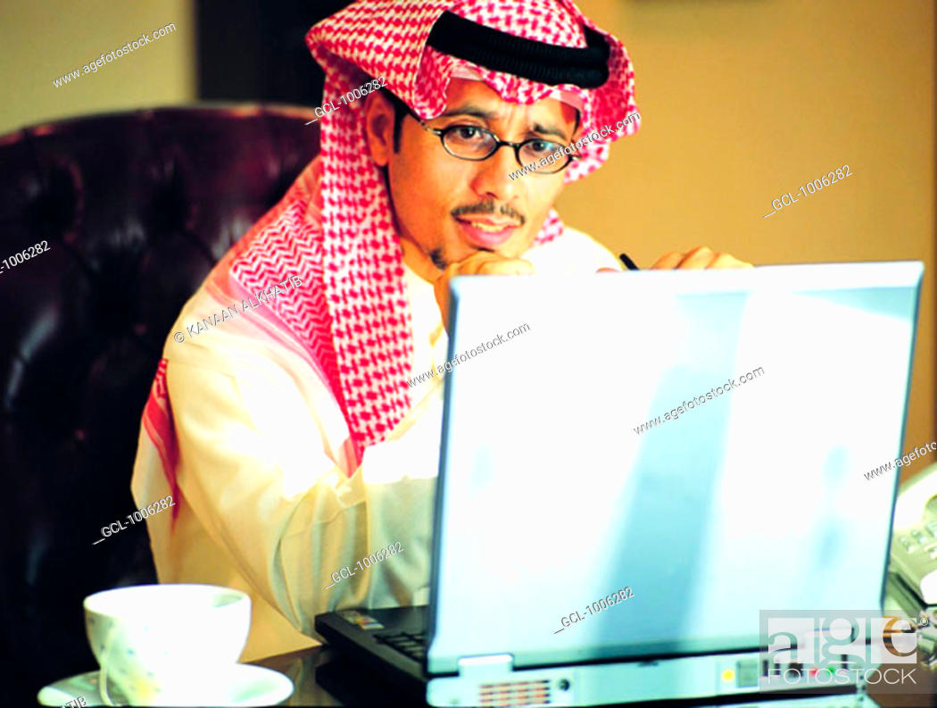 Stock Photo: Saudi businessman working on laptop.