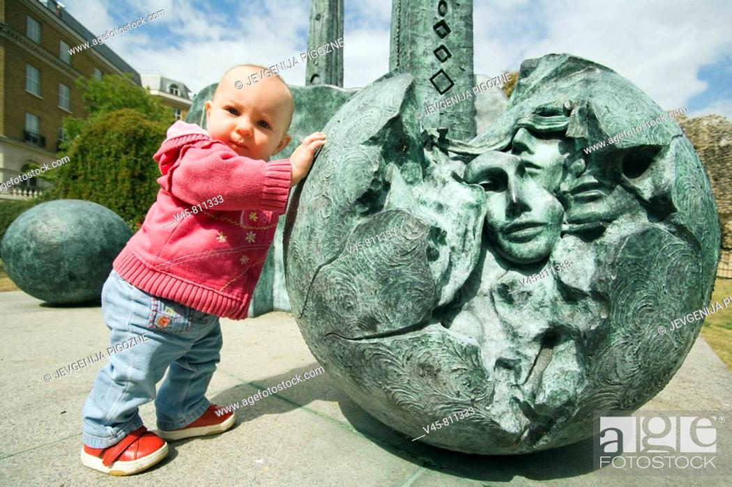 Stock Photo: Baby girl pushing a ball of the contemporary sculpture near Reading Abbey Berkshire, England.