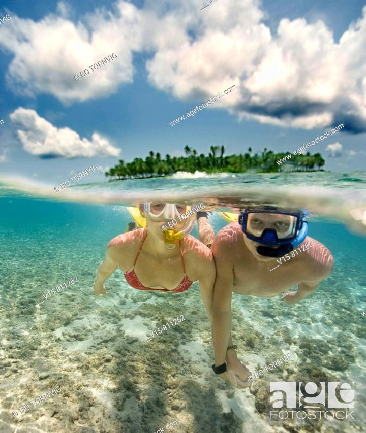 Stock Photo: couple swimming in front of remote tropical island.