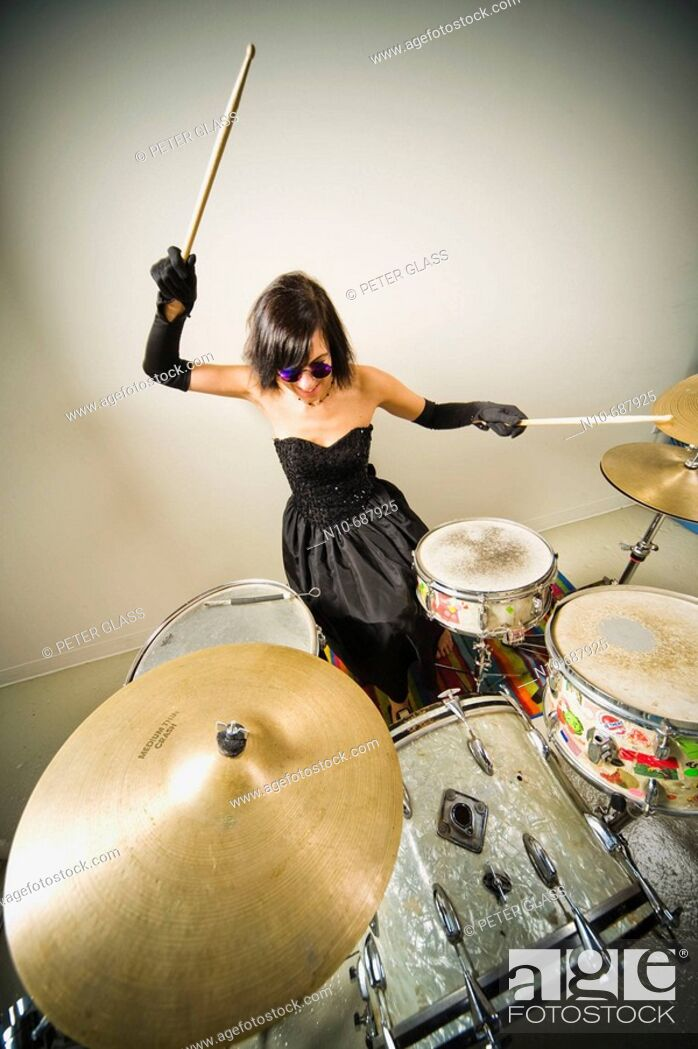 Stock Photo: Woman, wearing an evening gown and blue sunglasses, playing the drums.